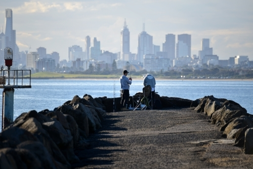 Two blokes fishing at the end of a pier with the city skyline in the background