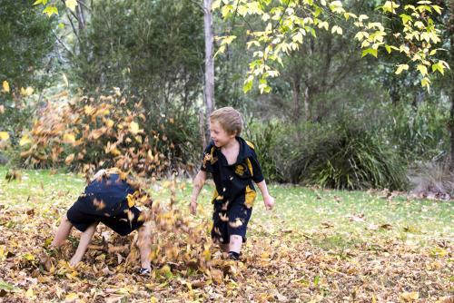 Two boys paying in autumn leaves wearing school uniform