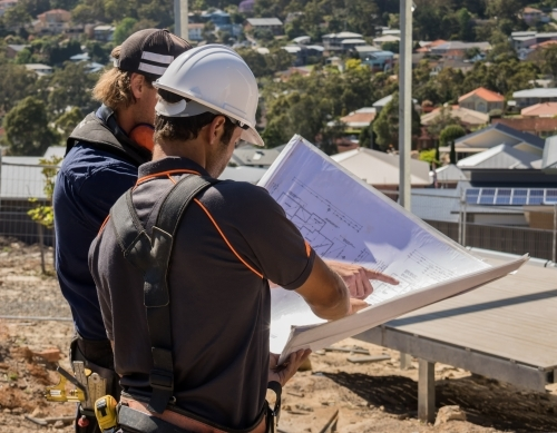 Two builders standing on building site, discussing architectural plans for new house