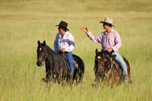 Two cattlemen on horses ride through tall grass discussing plans