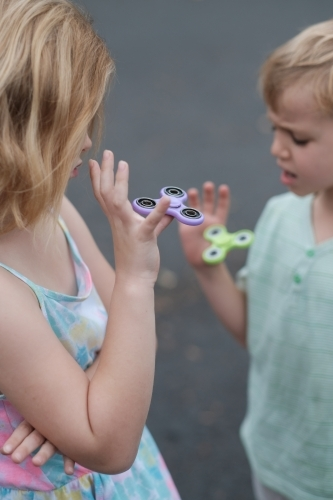 Two children playing with fidget spinner toys