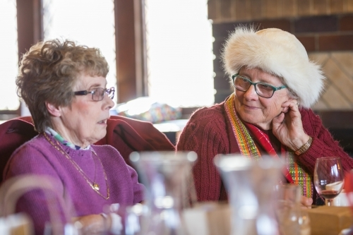 Two elderly women sitting and talking together at a restaurant