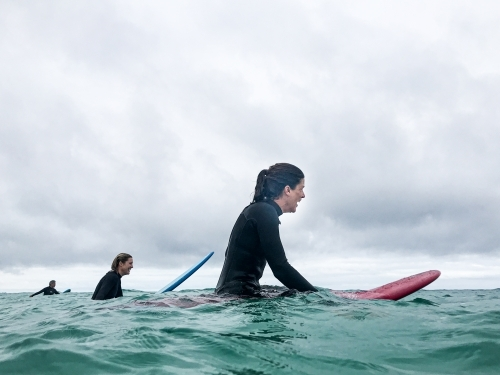 Two female surfers waiting for next wave on surfboards in ocean