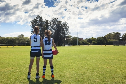 Two girl AFL players standing on the football ground