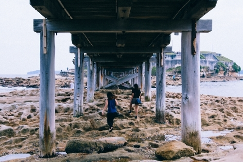 Two girls exploring under a bridge over rocks and water