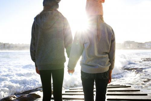 Two girls hold hands on a boat ramp by the ocean in the afternoon light