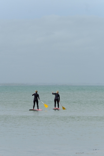 Two girls on stand up paddleboards on the ocean