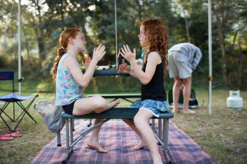 Two girls playing a clapping game at a campsite
