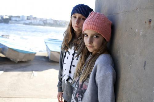 Two girls standing against brick wall posing by the ocean
