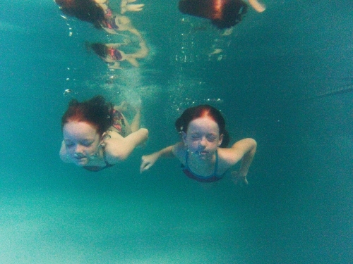 Two girls swimming underwater in a pool