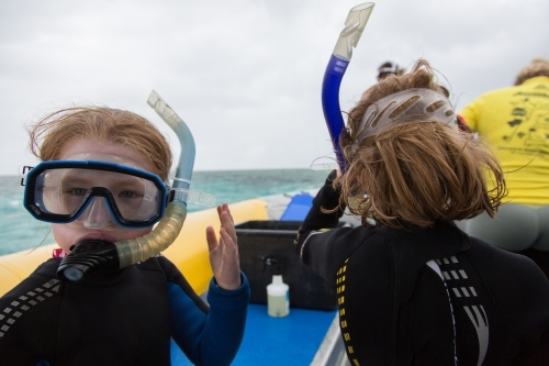 Two girls wearing masks, snorkels and wet suits