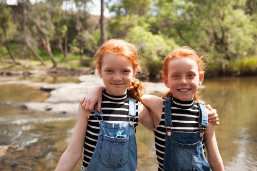 Two girls with arms around each other at the river