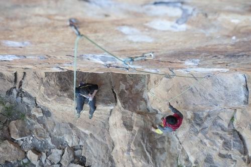 Two male rock climbers below route