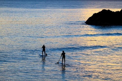 Two mature men paddleboard SUP near Norries Head at Cabarita Beach, NSW