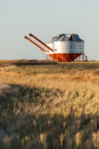 Two metal field bins sitting next to one another in a farmers paddock