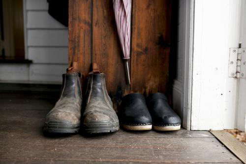 Two pairs of shoes lined up inside doorway of home