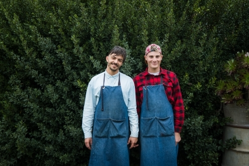Two partners at work in their aprons smiling.