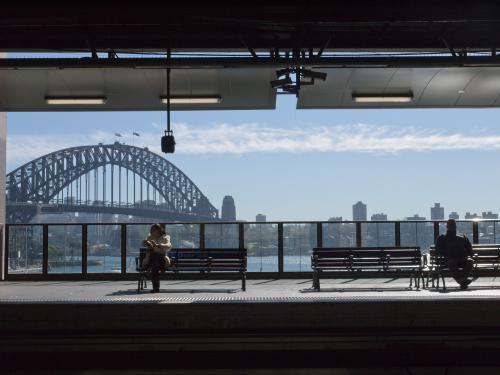 Two people waiting at Circular Quay Railway Station with the Harbour Bridge in the background