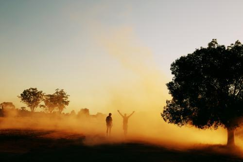 Two people walking through dust in the country.