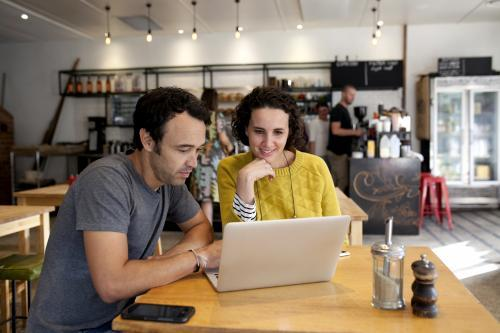 Two people with laptop at a cafe