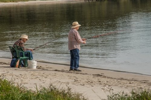 Two seniors enjoying fishing off a sandy beach on a sunny afternoon