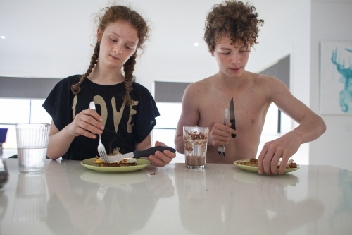 Two teenage children eating breakfast at home