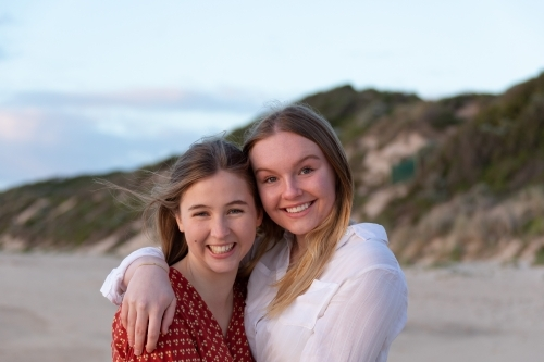 Two teenage girls embracing on the beach