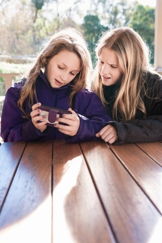 two tween girls looking at a phone