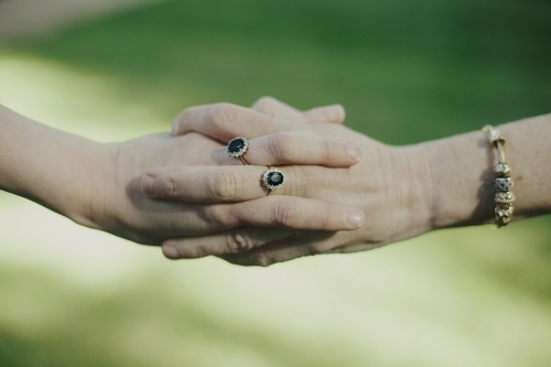 Two women holding hands wearing matching rings