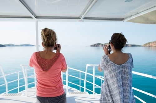 Two women on bow of pleasure cruiser boat on glassy still ocean whale watching taking photos