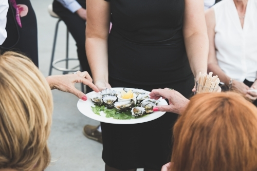 Two women's hands reaching for oysters from a platter being served by a waitress