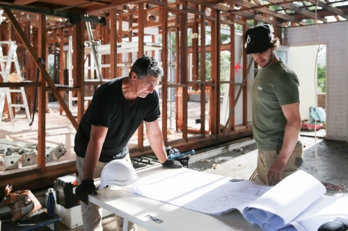 Two workers inspecting plans on a building site