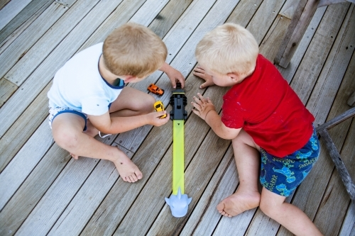 Two young boys play with cars on wooden decking viewed from above.