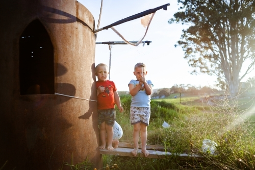 Two young boys stand next to a homemade water tank cubby house as afternoon sunlight shines in.