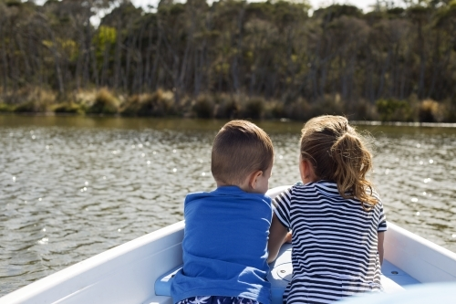 Two young children sitting in a row boat on the water
