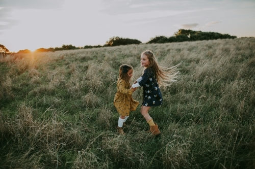 Two young fashionable sisters playing in a paddock at sunset