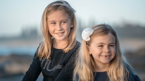 Two young girls close up at the beach