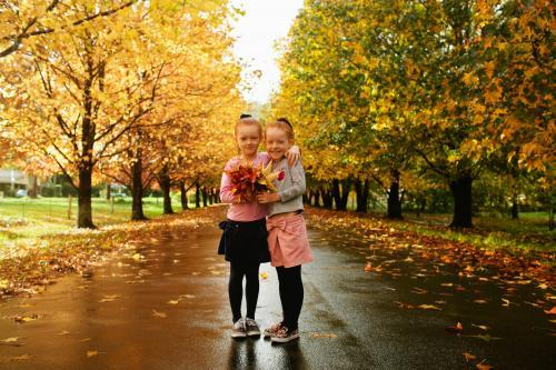 Two young girls holding autumn leaves on a tree lined street.