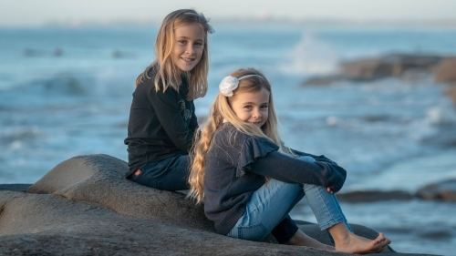 Two young girls sitting on rock at beach