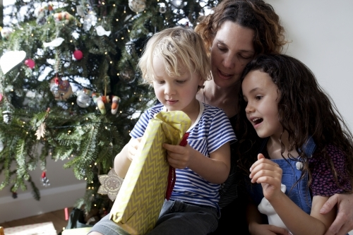 Two young kids opening presents on christmas with aunty