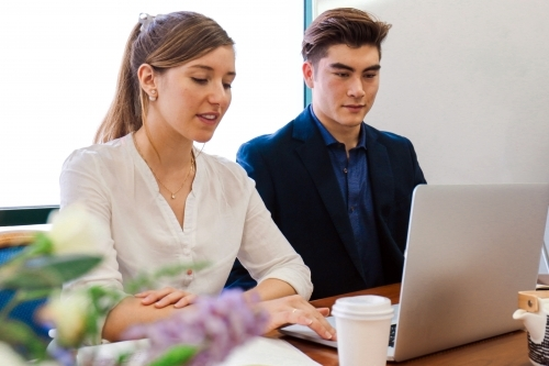 Two young professional office workers sitting at a meeting table with laptop