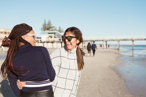 Two young women laughing on a beach