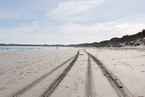 tyre tracks and footprints on a beach with people in distance