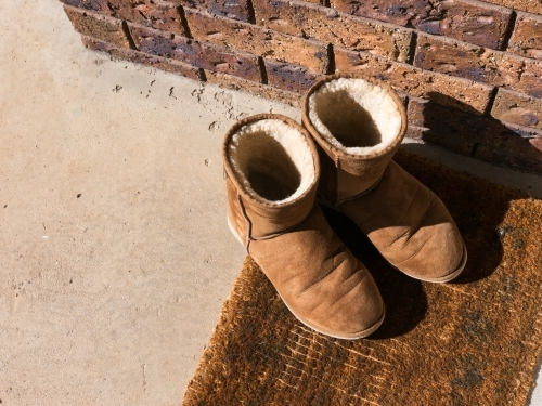Ugg boots on a worn brown front door mat