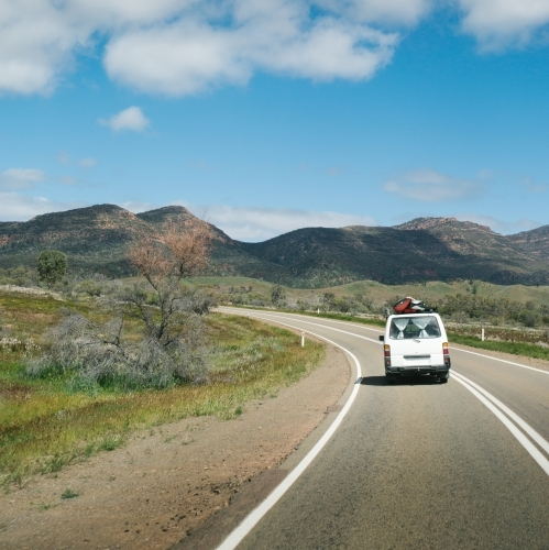 Van driving along a rural outback road from behind