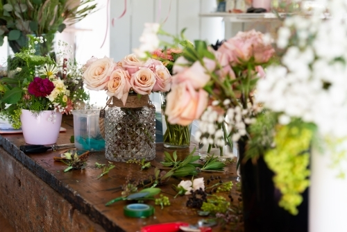 Vases of beautiful pink roses and other flowers with selective focus