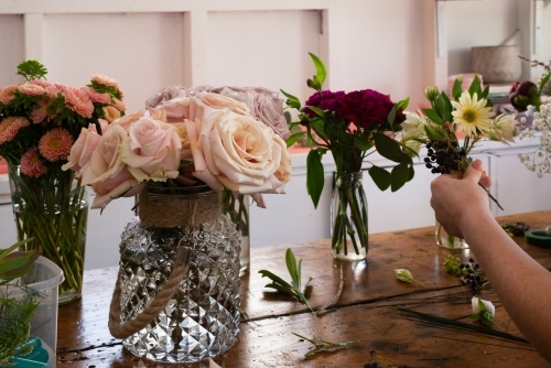 Vases of roses and other flowers on an old wooden work bench with womans hand holding arrangement