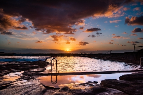 Vibrant sunrise colours in the sky over the ocean pool