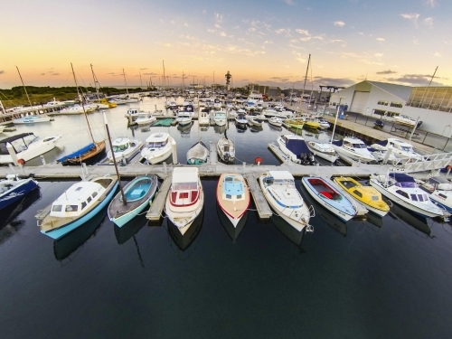 Looking down over yachts and boats in a marina at sunrise.