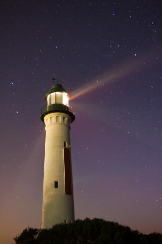 Light beams from a lighthouse at night